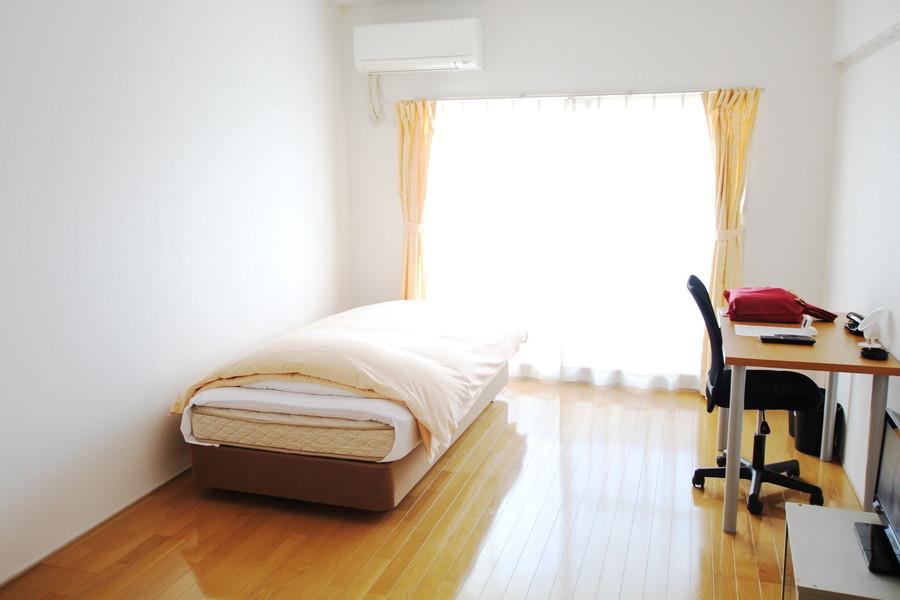 イエローブラウンのフローリングと白い壁紙のシンプルであきのこないお部屋