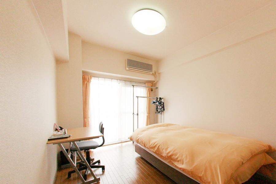 洋室にはベッドと作業デスク、パイプハンガーをご用意しています