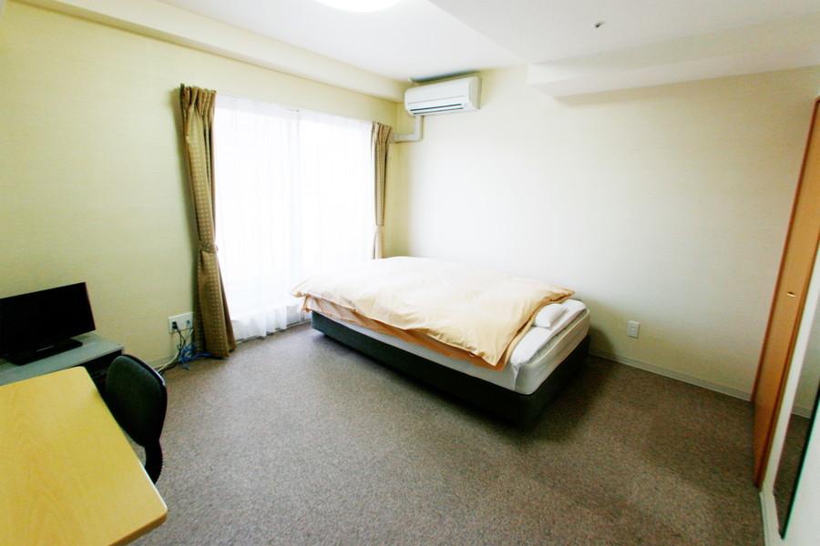 パープルグレーのカーペットが落ち着いた印象を与える室内