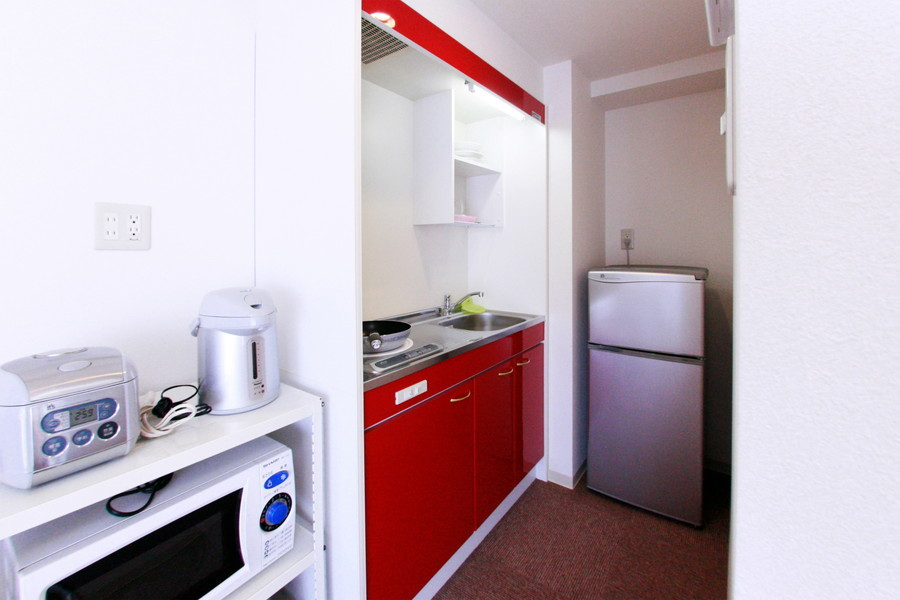 お部屋の奥にはコンパクトキッチン。インパクト抜群の赤が眩しいです