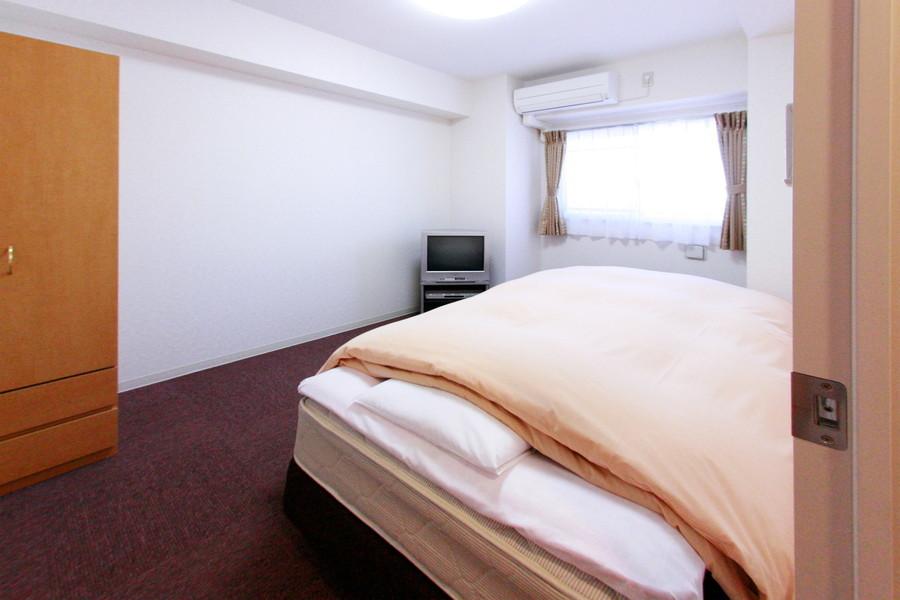 寝室は高い天井と小窓で開放感アップ。収納家具も完備されています