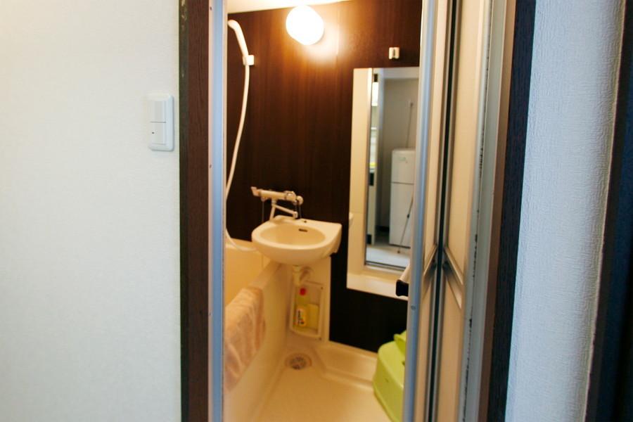 木目の壁と大きい鏡が印象的なバスルーム