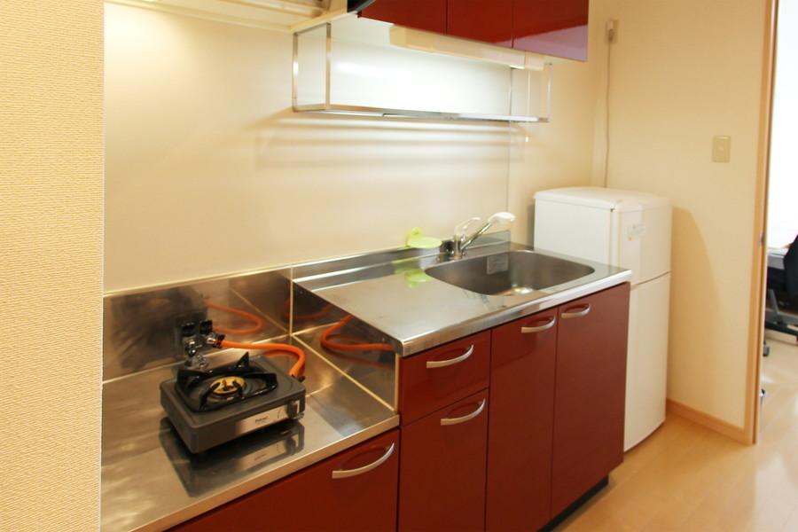 深い赤が印象的なキッチン。シンクや作業スペースも広くお使いいただけます