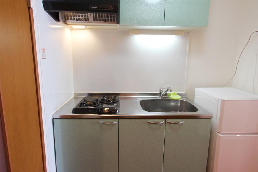 ペールグリーンの棚がカラフルなキッチン。ワンルームでは珍しい2口コンロです