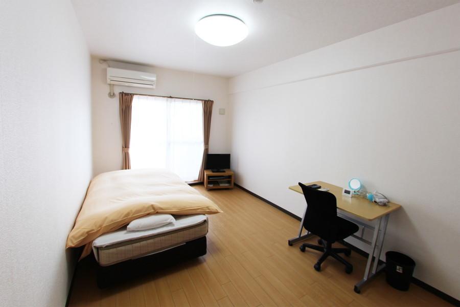 淡いブラウンのフローリングと白い壁紙のシンプルで住みやすい色合い