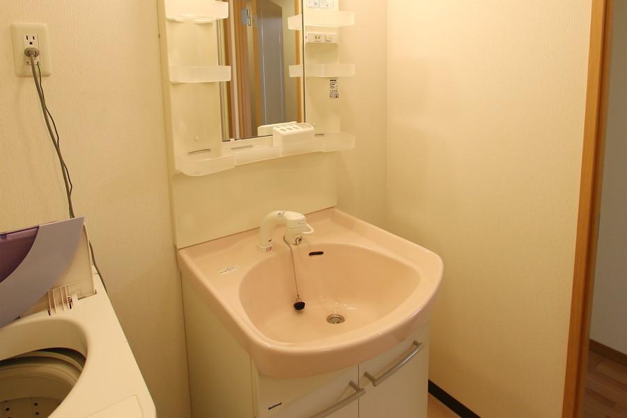 小物収納スペースたっぷりの洗面台。ピンクの洗面ボウルがキュートです