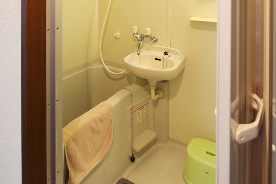 白を基調としたバスルーム。バスマットや洗面器もご用意しております