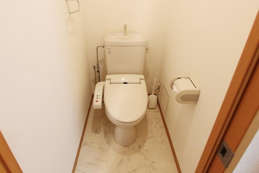 大理石模様の床に落ち着いた高級感を感じる、白を基調とした清潔感のあるお手洗いです。