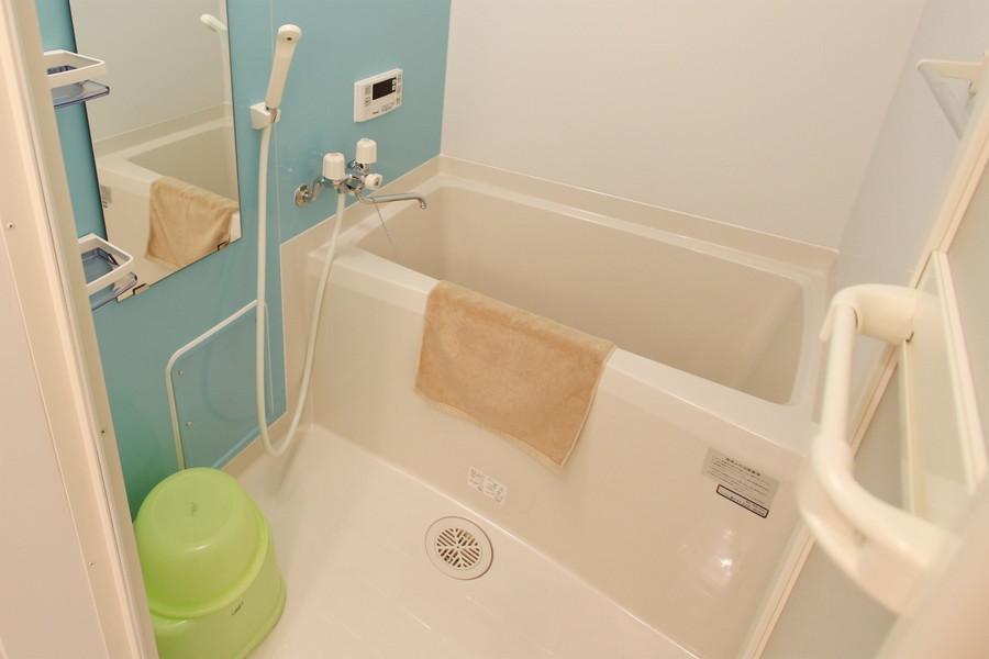 清潔感溢れるバスルーム。水色の壁でさわやかな印象をプラス