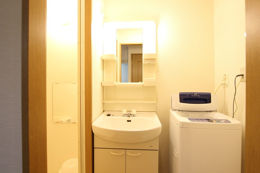 シンプルで清潔感のあふれる白の洗面台。鏡付きで身だしなみはバッチリ。