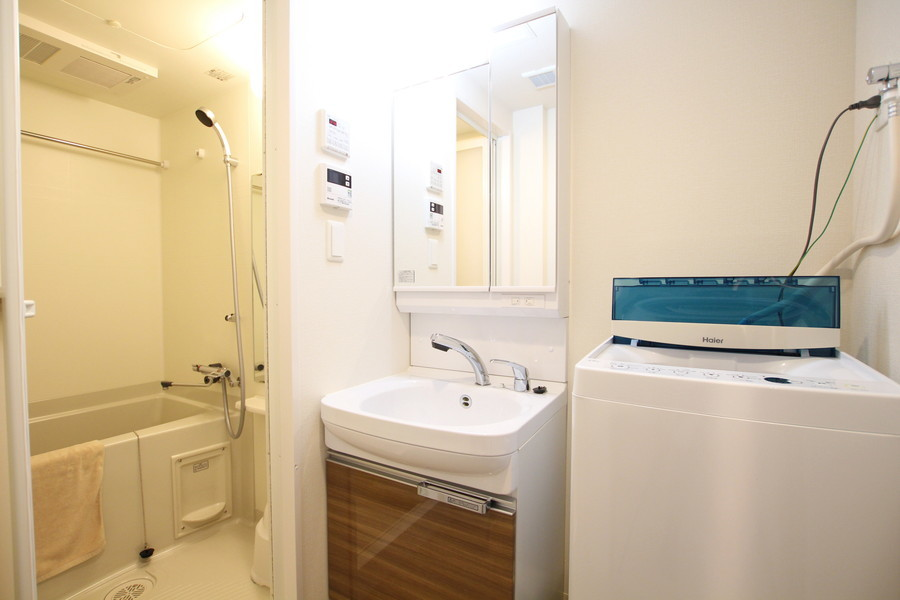 大きな鏡の明るい洗面台で身だしなみもバッチリ。ブラウンの木目の落ち着いた雰囲気と、清潔感のある白の組み合わせが印象的。