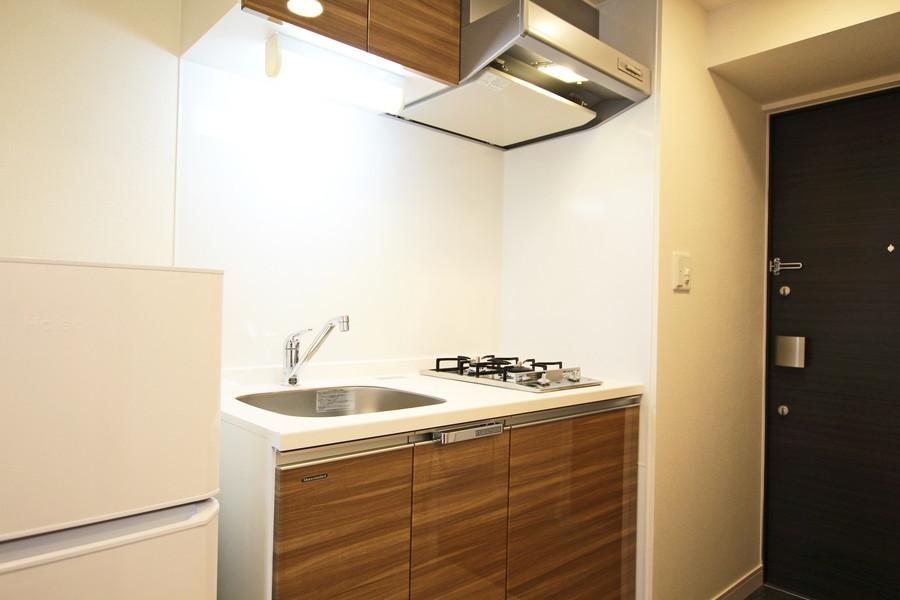 木目の棚が落ち着いた雰囲気のコンパクトキッチン。使い勝手の良い2口ガスコンロです。