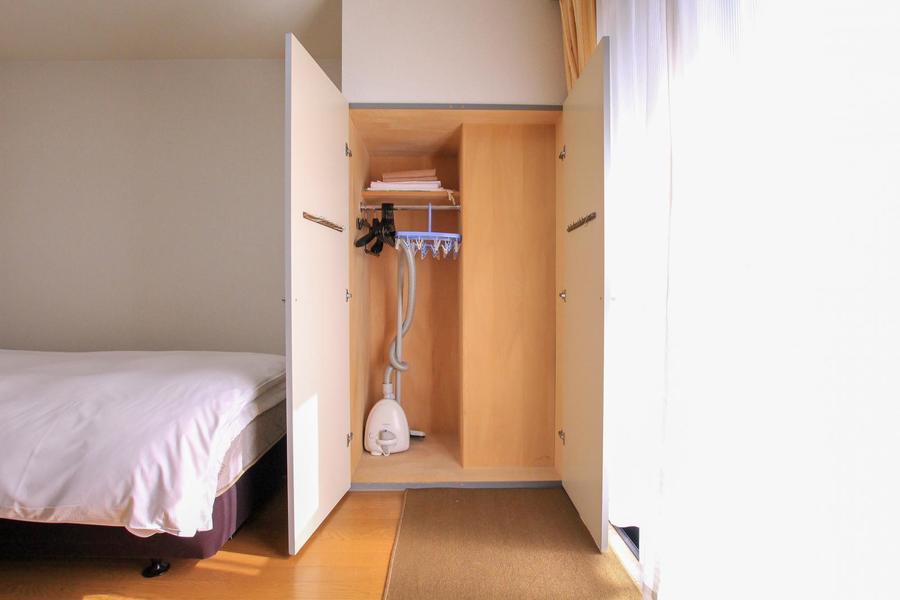 ベッド横のクローゼットはハンガー付き。コートやスーツの収納に!