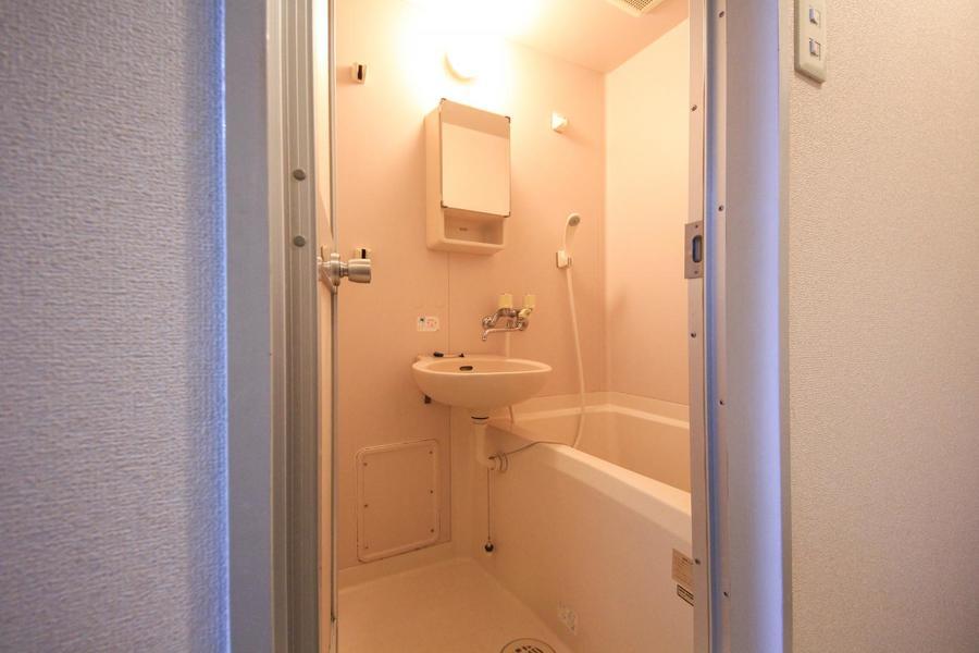バスルームは清潔感あふれる空間。鏡付きの収納棚がポイントです