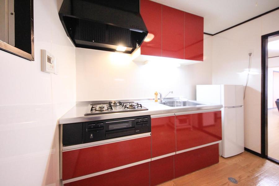 赤い戸棚が印象的なシステムキッチン。ガスコンロはビルトインタイプです