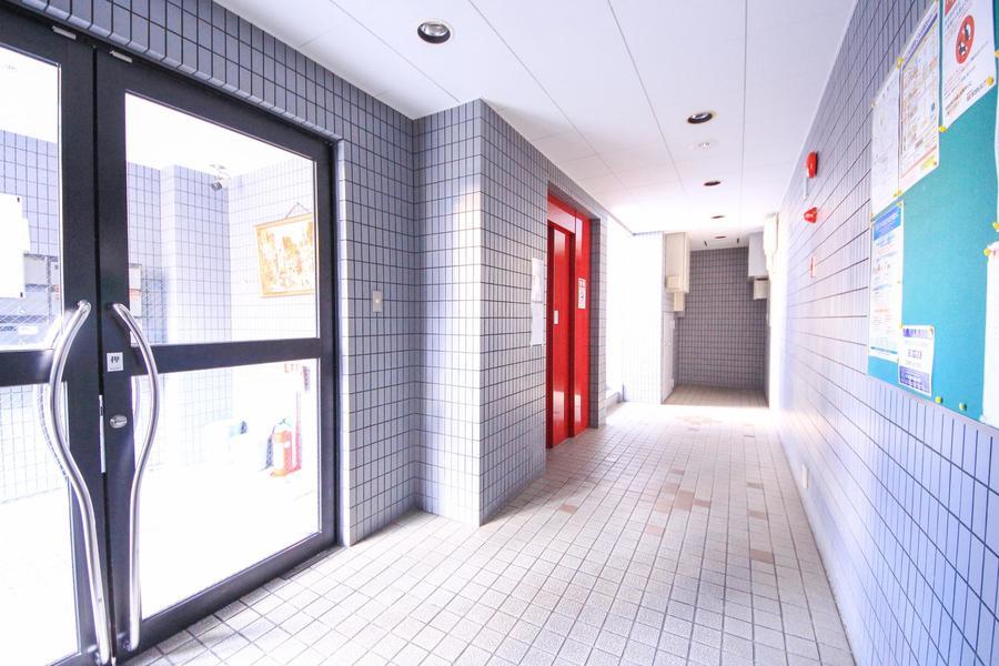 薄くグレーがかった壁面の中真っ赤なエレベータードアが目を引きます