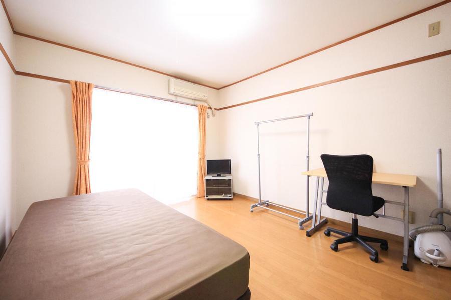ライトブラウンのフローリングと白い壁紙のシンプルで明るいお部屋