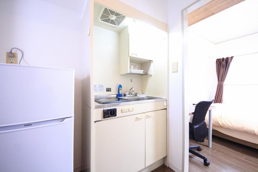 キッチンはコンパクトタイプ。便利な吊り棚も設置されています