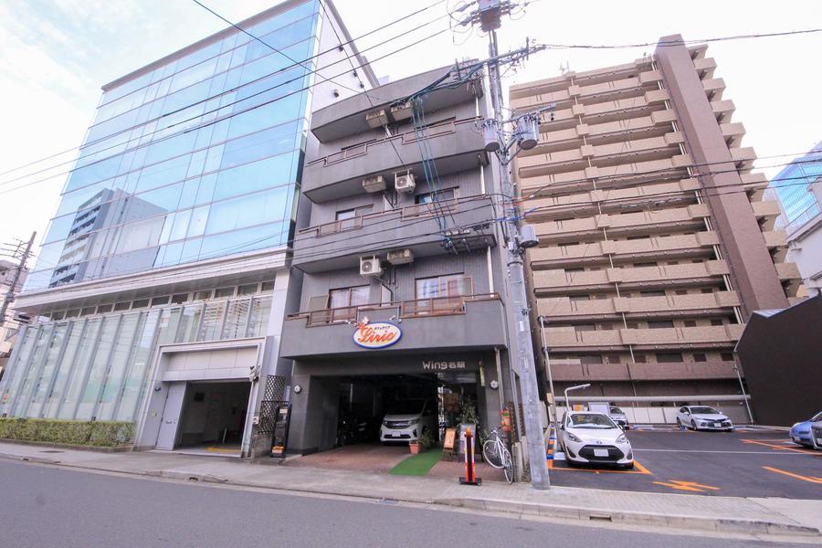 グレーの外壁が特徴。周囲はマンション、商社ビルなどが立ち並びます