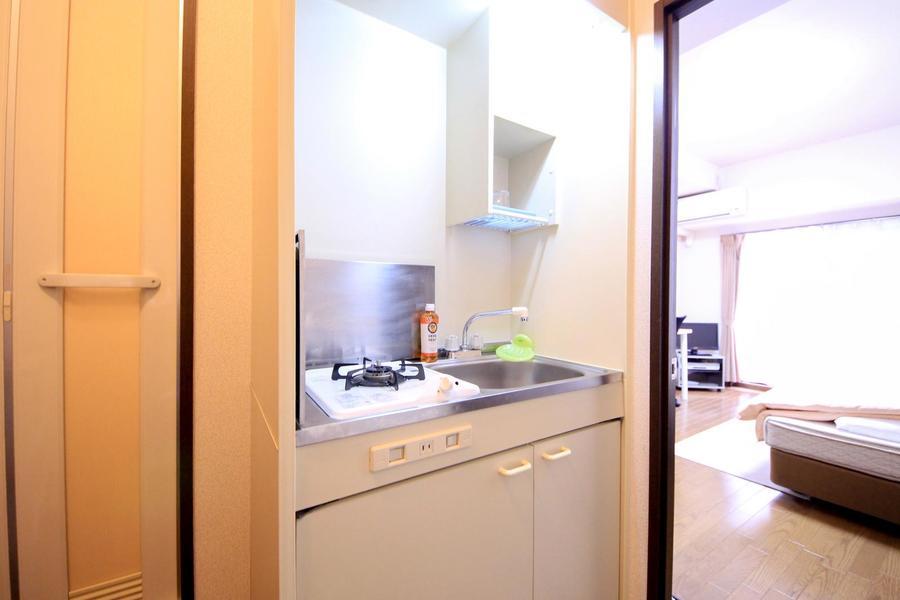 キッチンはコンパクトタイプ。収納に便利な吊り棚つきです