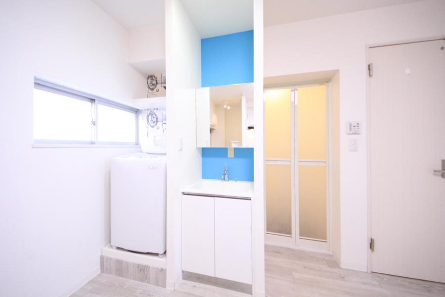 大きめの鏡がポイントの洗面台。ブルーの壁紙がカラフルです
