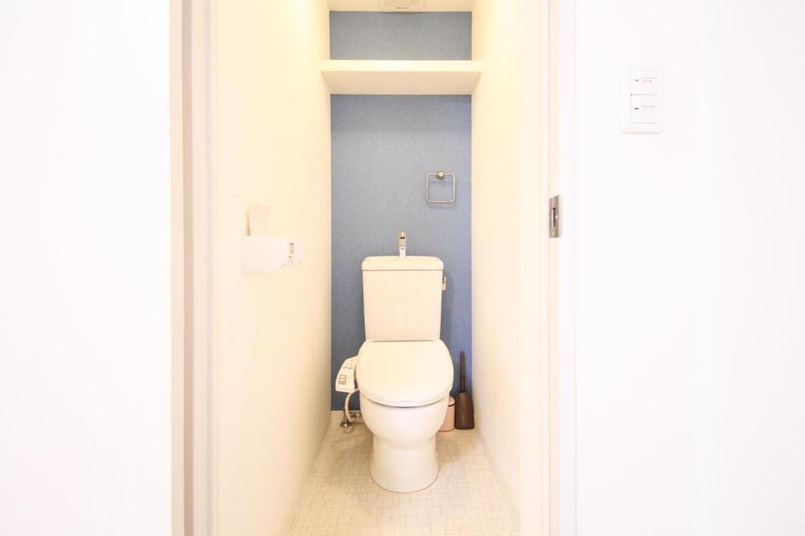 お手洗いはウォシュレット式。くすみブルーのクロスが空間を引き締めます