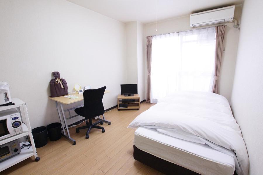 白の壁紙と木目の床の組み合わせ。シンプルながら居心地の良いお部屋です