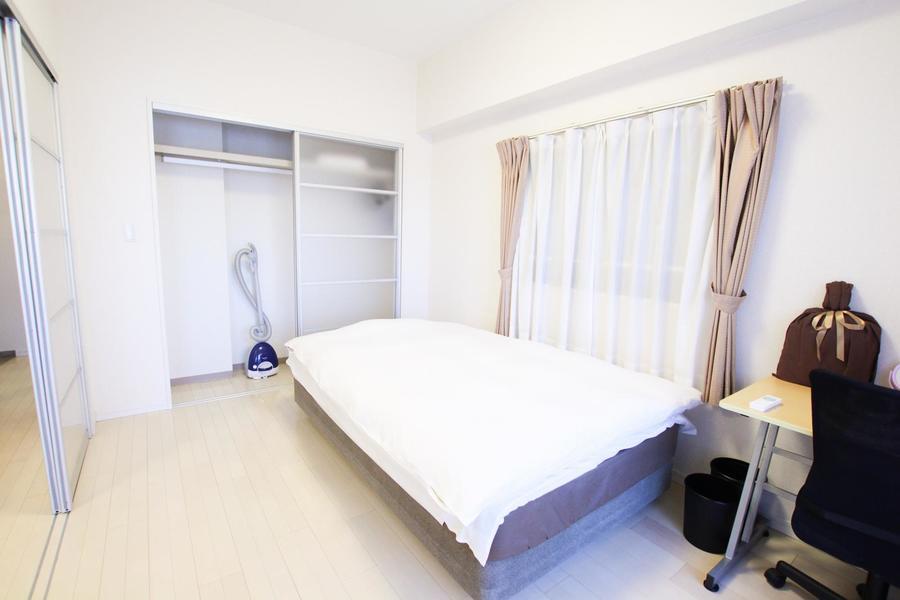 寝室はリビングと同じくベージュのフローリングに白を基調としています