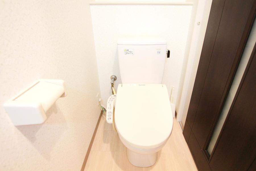 ドアの木目が落ち着いた雰囲気のお手洗い。小物収納スペースも完備