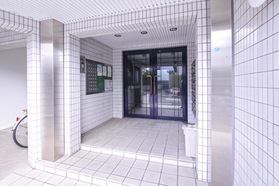 ホワイトタイルにネイビーブルーのドアが映えるシックな雰囲気のエントランス