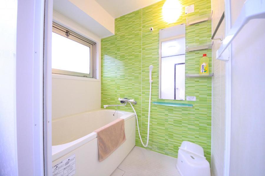 清潔感溢れる洗面所から一転、緑のアクセントクロスが映えるバスルーム