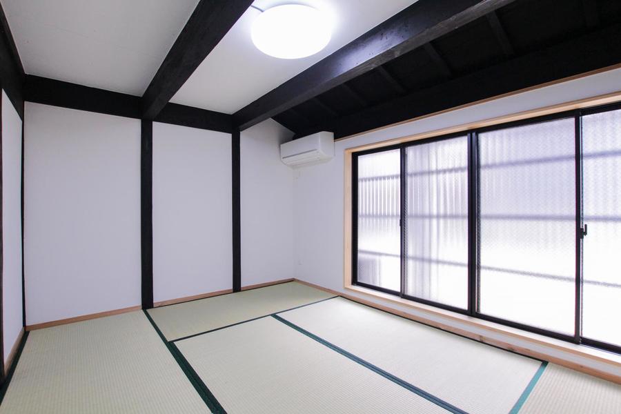 白壁と黒い木材が趣ある空間を演出するくつろぎの和室。窓の外には四間道の情緒ある町並みが広がります。