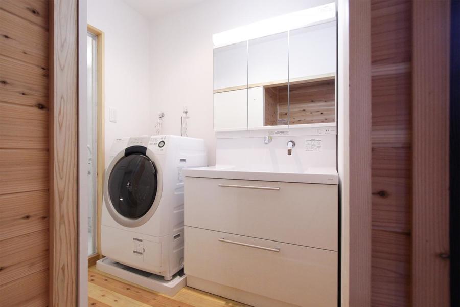 大きな鏡の付いた広々使える洗面台。横には大きなドラム式洗濯機があり、たくさんの洗濯物にも困りません。