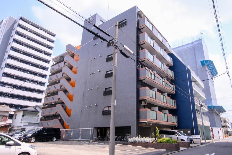 ちらっと見えるオレンジの壁が映えるベーシックな建物