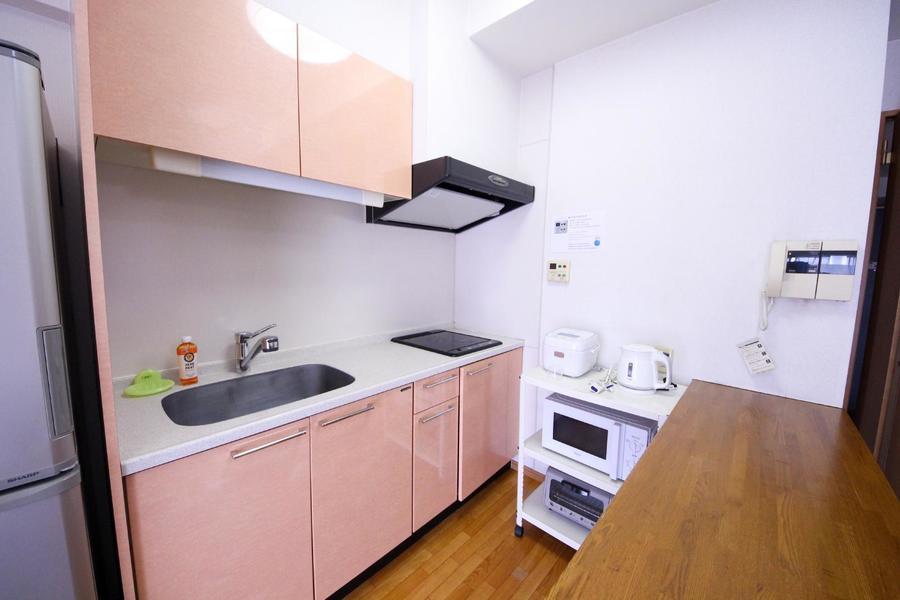 カウンターテーブルの向こうはキッチン。ライトピンクの扉がキュート