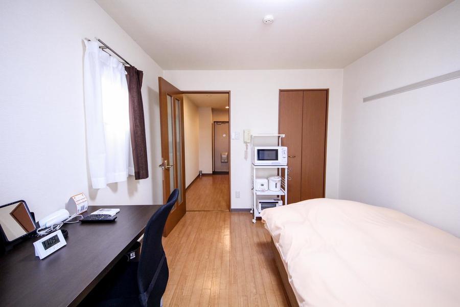 シンプルな室内にブラウンのドアがアクセント