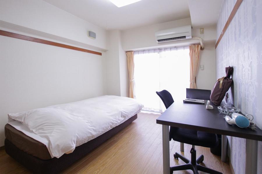 淡いブルーの壁紙が落ち着いた雰囲気を演出する、明るく広々としたお部屋です。