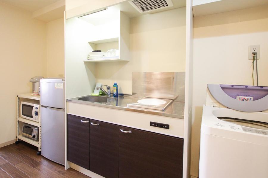 コンパクトキッチンは木目の扉がポイント。食器類もご用意しています