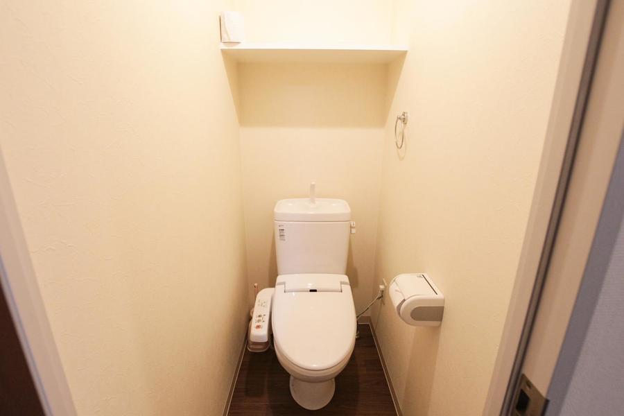 木目の床面が落ち着ける雰囲気のお手洗い。上部に棚があり小物を置くことができます。
