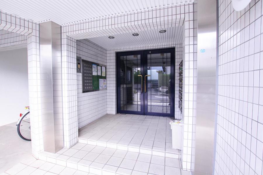 ホワイト系のタイル張りの丸みを帯びた外観デザイン。入口の緑が安らぎをそえます。日当たりも良く住環境は抜群です。
