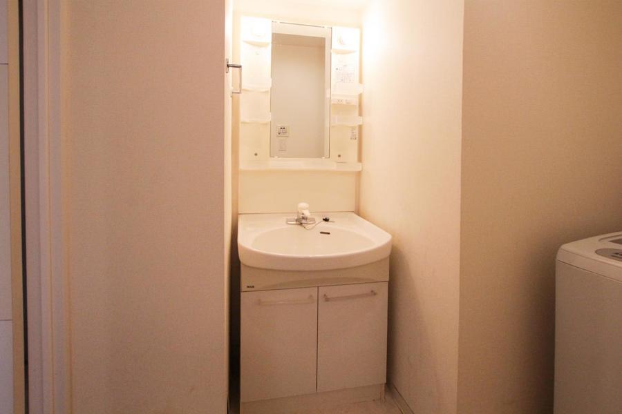 シンプルで清潔感のあふれる白の洗面台。シャワー・鏡付きで身だしなみもバッチリ。