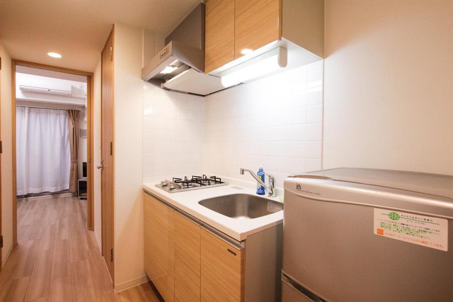 床面やドアにそろえた木目がおしゃれな2口ガスコンロのシステムキッチン