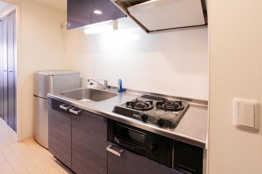ネイビーブルーのパネルが印象的なキッチン。高級感と清潔感を感じさせます
