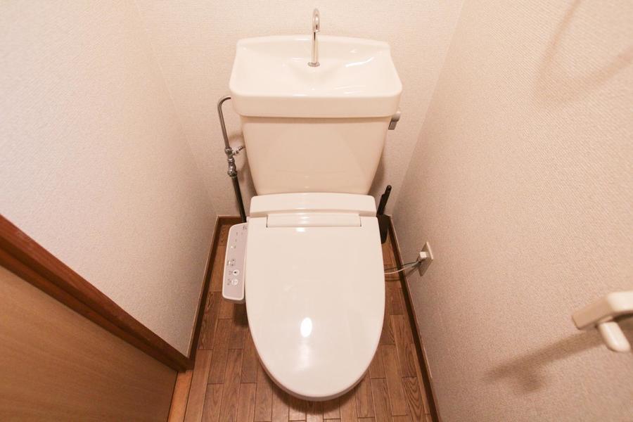 ドアや床面の木目が落ち着ける雰囲気。清潔感のあるお手洗いです。