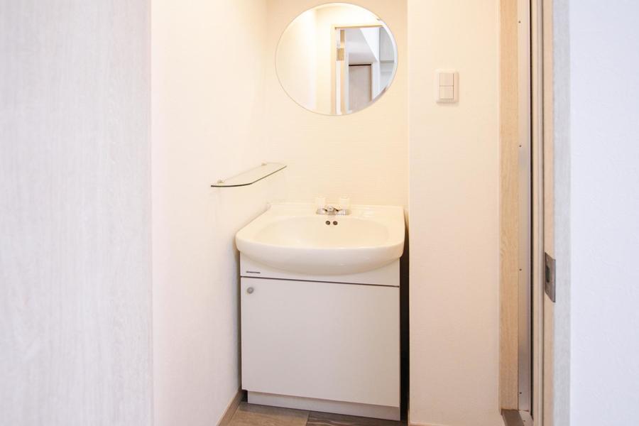 丸い鏡とガラスの棚がおしゃれな洗面台。明るく清潔感にあふれています