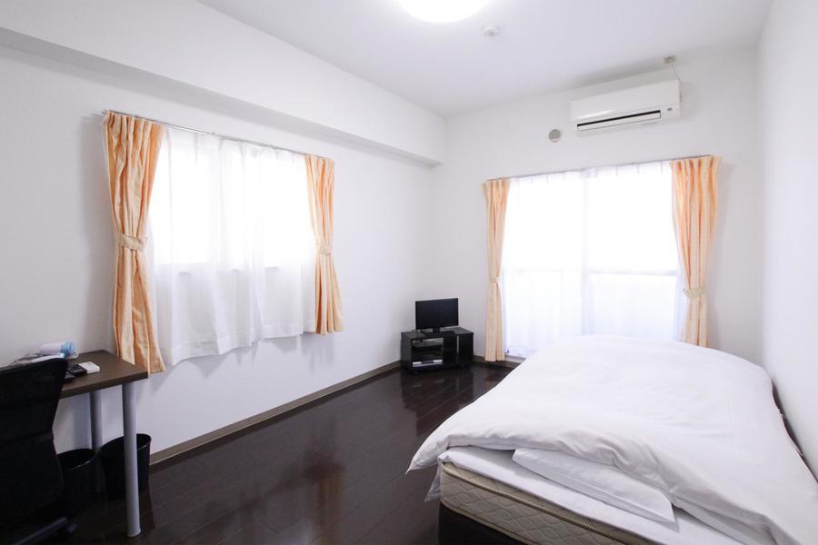 ダークブラウンのフローリングに白を基調とした落ち着いた雰囲気のお部屋です