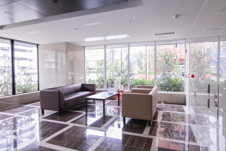 つややかな床と革張りのソファが映えるエントランスルーム