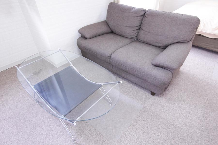 チャコールグレーのゆったりソファ。ガラスのローテーブルもオシャレです