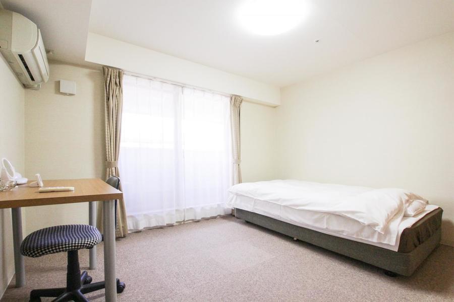 ゆったりと広めのベッドルーム。シックな色合いで落ち着けるお部屋です
