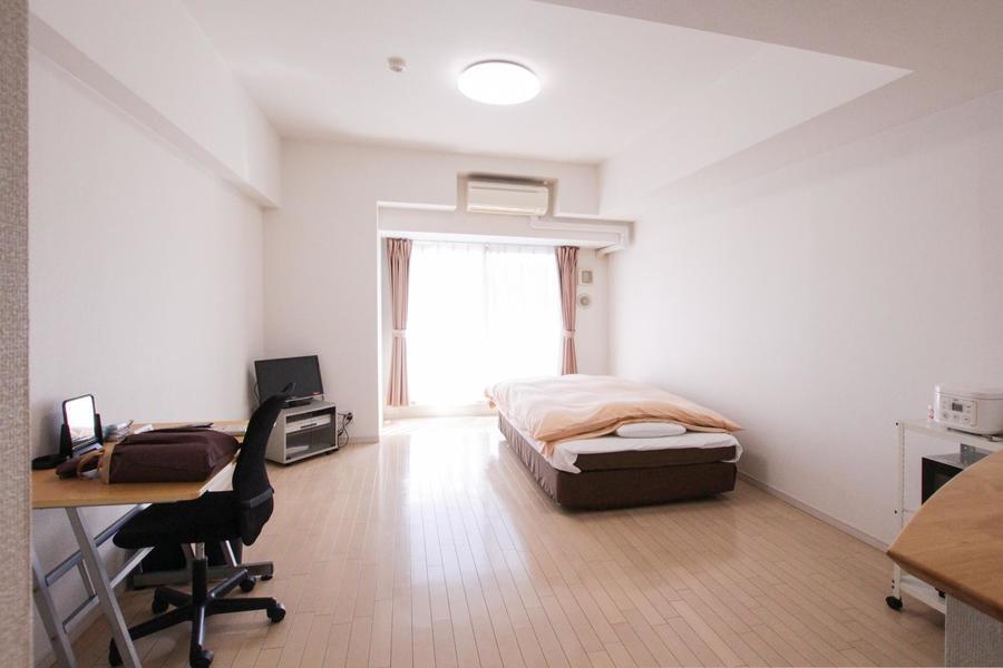 淡い色合いのフローリングと白い壁が明るい印象の広々としたお部屋